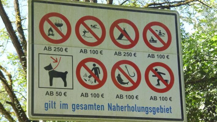 Schild mit Strafen für Ordnungswidrigkeiten im Wald